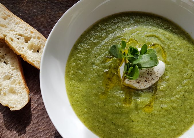 a green soup with bread on the side
